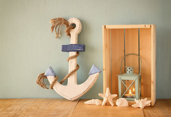 Old nautical wood anchor, lantern and shells on wooden table ov