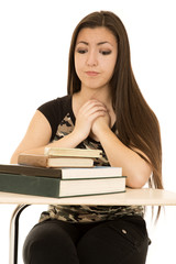 Female student lokking at her books hands clasped