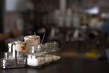 Sugar bowls on the black tabke in a bar