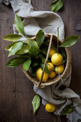 fresh lemons with leaves on straw basket on wooden table