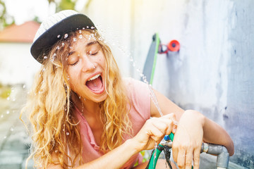 woman drinking from a hose after skating