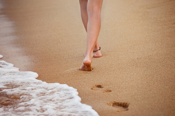 Healthy young woman is walking on the yellow sand leaving footpr
