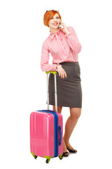 Business woman in business trip with a suitcase on wheels speaki
