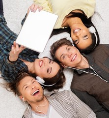 Happy multiracial friends taking selfie with tablet pc