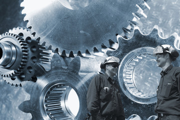 Wall Mural - engineers working with large cogwheel machinery in background