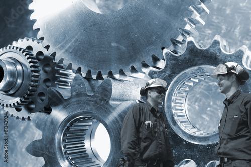 Wall mural engineers working with large cogwheel machinery in background