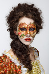 Venetian mask. Beautiful woman in vintage dress and a mask on hi
