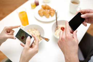 close up of couple with smartphones at breakfast