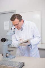 Scientist analysing microscope writing on clipboard