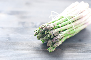 Group of fresh green asparagus on cutting board.