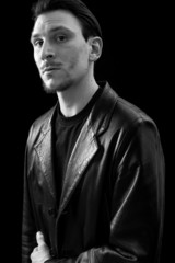 Male portrait wearing leather coat and looking black and white