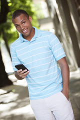 Young happy african american man sending text message