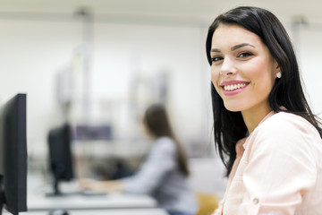 Young beautiful woman smiling happily in a classroom