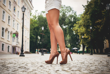 woman legs in brown high heel shoes and shorts outdoor shot