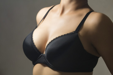 Woman wearing a black brassiere isolated on a gray background