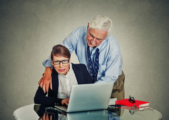elderly businessman harassing his young colleague woman