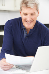 Smiling Mature Man Reviewing Domestic Finances