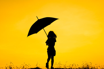 Umbrella girl with sunset silhouette