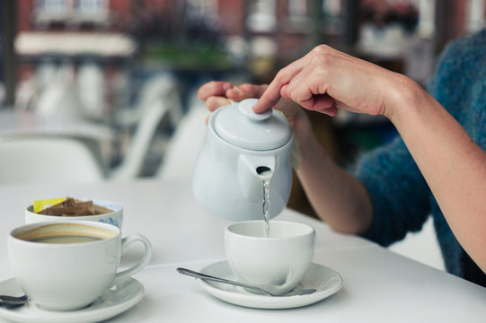Young woman pouring a cup of tea