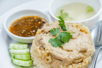 Rice roast chicken with spoon and fork on white plate.