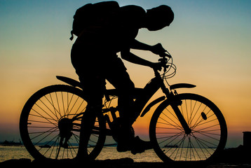 Silhouette of backpacker ride mountain bike on bridge beside sea