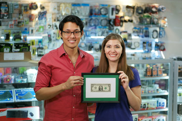 Portrait Of Happy Shop Owners Showing First Dollar Earning