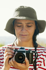 woman with hat takes photos with old camera