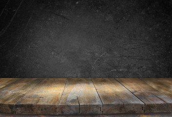 Grunge vintage wooden board table in front of black textured bac