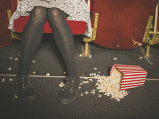 Woman in theater with popcorn on the floor