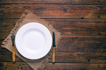 empty white plate fork and knife on rustic wooden background