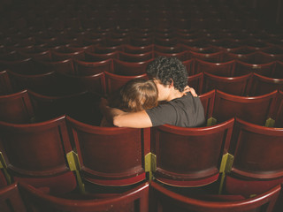 Young couple kissing in movie theater
