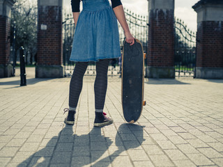 Young woman standing at gates of park with skateboard