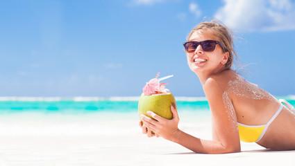 young woman smiling lying in bikini with coconut on beach