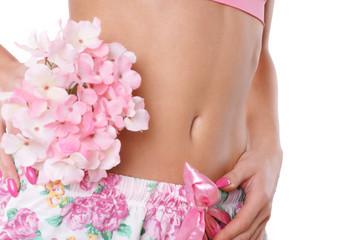 flacher Bauch einer Frau mit Blumen