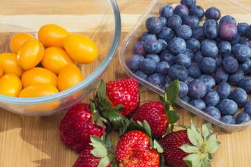 kumquat, strawberries and blueberries on a cutting board
