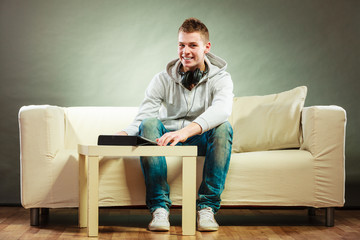 man with headphones sitting on couch with tablet