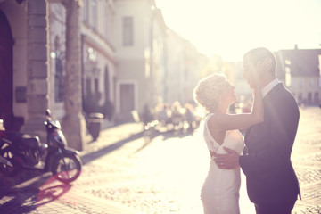 Bridal couple holding each other at sunset in old city
