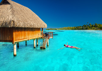 Young woman swimming in tropical lagoon next to overwater villa Wall mural