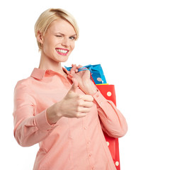 Woman holding shopping bag and showing ok, isolated on white bac