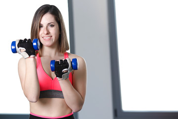 beautiful young girl doing exercise at gym with weights