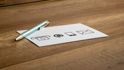 Pen and contact icons printed on a white card