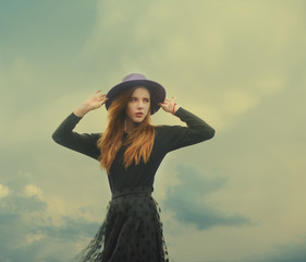 beautiful girl in a hat on a windy day
