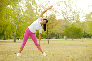 Young woman warms up by doing stretching exercises in a park.