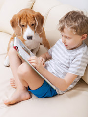 Boy reading for his dog at home