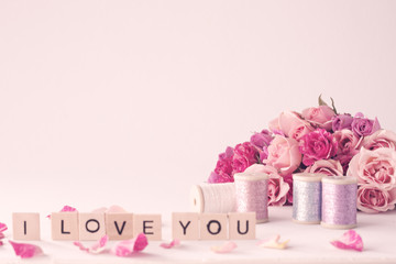 Vintage pink peonies and love message over beige background