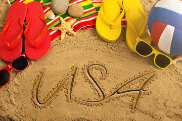 Summer concept of sandy beach, colorful thongs shoes, sunglasses