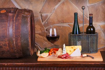 Glass and bottle of wine, cheese and prosciutto