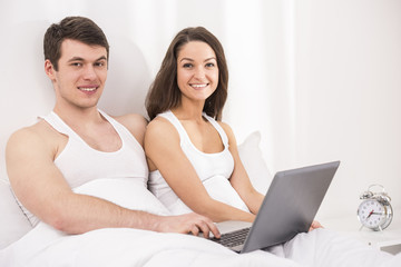 Smiling young couple using laptop in bed.