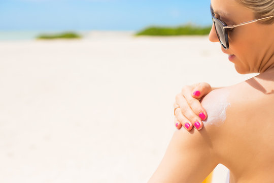 Woman applying sunscreen at the beach on hot summer day