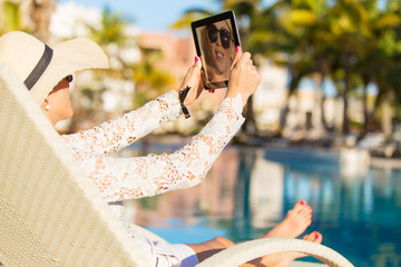 Woman taking selfie with tablet computer while on vacation